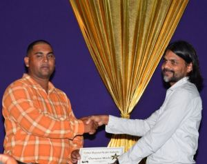 A proud sponsor of the event, Yog Mahdeo handing over the champion worker award to driver/mechanic Perry Phillips