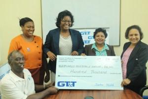 Principal Tutor Mr. Hillary Christopher and Senior Tutor Ms. Sabina Gullin accept the donation cheque from GT&T Senior Marketing Officer Anjanie Hackett.