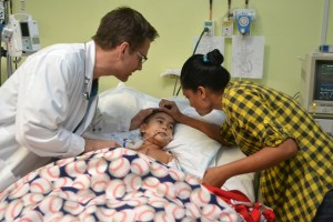 A patient recovering and being comforted by his mother and a doctor.