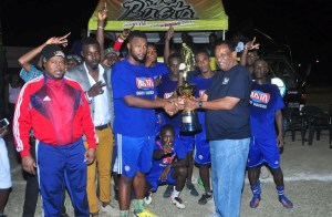 Managing Director of the Guyana Beverage Inc., Robert Selman, presents the championship trophy to members of the Sparta Boss team. Sharing the moment is director of the Petra Organisation, Troy Mendonca.