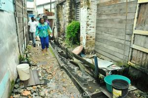 Minister of Social Protection, Ms. Volda Lawrence making her way through an alley at Lombard and Board streets to get a first hand view of the living conditions at that location.