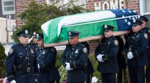 New York City police officers carry the coffin with the remains of slain police officer Randolph Holder
