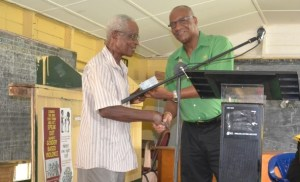 Minister of State, Joseph Harmon handing over the cheque to Mr. Bowman, resident of Crane Housing Scheme.