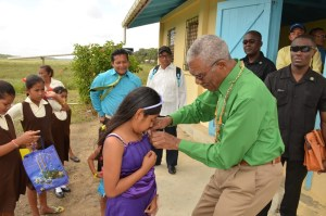 A little girl receives a pin from the President of Guyana after placing a garland on his neck at Akawini