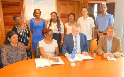 Ambassador Videtič and Ms Madray affix their signatures to the contract in the presence of EU Delegation and Childlink Inc officials