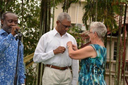 General Secretary of the Guyana Red Cross Society, Ms. Dorothy Fraser pins the Red Cross badge on President David Granger's shirt to formally induct him as patron. (Russel Lancaster, who chaired the event, is pictured left).