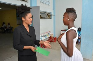 Public Information and Press Services Officer, Lloyda Nicholas-Garrett hands over $100,000 to mother of two, Cidel Hector, who lost all she owned in a house fire that has left her toddler son nursing first, second and third degree burns