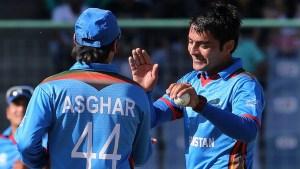Afghanistan's Rashid Khan, right, and Asghar Stanikzai celebrate the fall of England's Chris Jordan during their ICC Twenty20 2016 Cricket World Cup match at the Feroz Shah Kotla cricket stadium in New Delhi, India, (AP Photo/Manish Swarup)