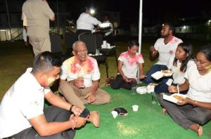 President David Granger partakes in the refreshments with the youths, after they indulged in some early Phagwah play, powdering each other with abrak.