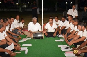 President David Granger tries his hand at the dholak (two-headed drum) during the Chowtal singing at State House