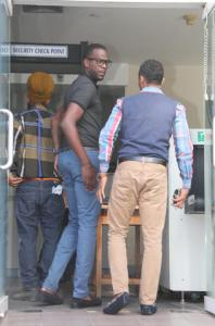 Caption: National cricketer Kevon Cooper, left, enters the Port-of-Spain Magistrates' Court yesterday. (PHOTO: RISHI RAGOONATH)
