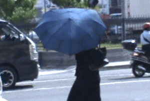 Keisha Chase hid herself from the media with a blue umbrella