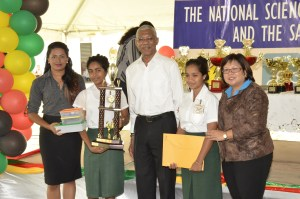 The Sagicor 2016 Champions: President David Granger is flanked by the inventors of the 'Eradicator' mosquito repellent; Ms. Dolly Sooknanan (left) and Ms. Darshanie Nanhu (right). Teacher of the Bygeval Secondary, Ms. Jaishree Nanku is at extreme left, while Sagicor's Communications Specialist, Ms. Marlene Chin is at extreme right.