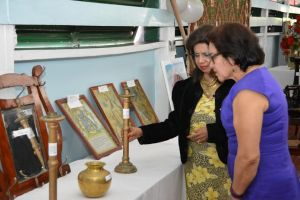 First Lady, Mrs. Sandra Granger takes a closer look at one of the candlesticks displayed at an exhibition hosted by the Dharm Shala as Ms. Kella Ramsaroop, Managing Director of the facility, explains its history.