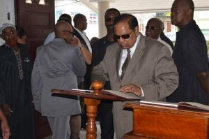 Prime Minister Moses Nagamootoo signing the Book of Condolence at the viewing of Haslyn Parris