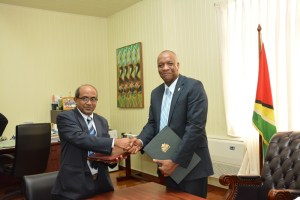 Indian High Commissioner to Guyana, Mr. Venkatachalam Mahalingam and Minister of State, Mr. Joseph Harmon shake hands after the signing, earlier today.