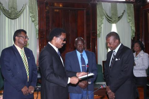 Attorney General Basil Williams presenting the Rodney COI Report to House Speaker Dr Barton Scotland. Looking on are Minister Khemraj Ramjattan and Clerk of the National Assembly Sherlock Isaacs