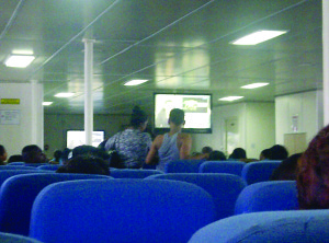A prisoner (in grey vest) chatting with a civilian on the ferry (Guyana Times photo)