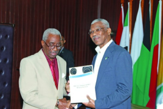 President David Granger receives a copy of the CoI report from Chairman of the Commission, retired Justice James Patterson on Wednesday at the Ministry of the Presidency