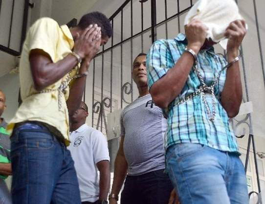 """Accused: Julius """"Demo"""" Balondemu and Ross Russell hide their faces as they leave the Port of Spain Magistrate's Court, yesterday. (Photo: KERWIN PIERRE, Trinidad Express)"""