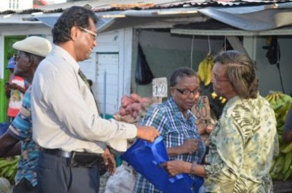 Public Security Minister, Khemraj Ramjattan distributing fliers and other items to raise awareness of trafficking in persons to members of the public around the Bourda Market area