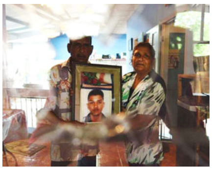 Krisha Sieunarine and wife Flora holding a photograph of their only son who was killed during a fight with Krishna four months ago.