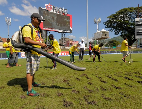 Ground staff use a blower to dry the field under the supervision of umpire Gregory Brathwaite (4L) during day 3 of the 4th and final Test between West Indies and India at Queen's Park Oval in Port of Spain, Trinidad on August 20, 2016. / AFP PHOTO / Randy BROOKS