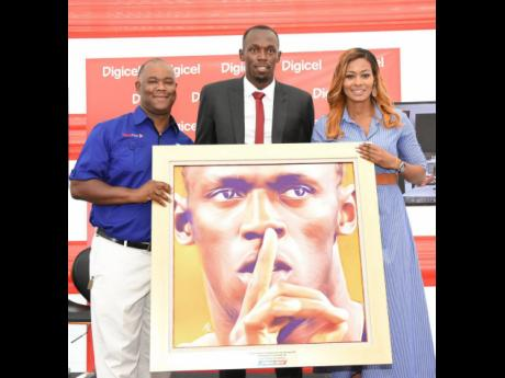 SportsMax CEO Oliver McIntosh (left) and SportsMax head of marketing Tanya Lee present Usain Bolt with a golden portrait on Tuesday during his first day at work as Digicel's Chief Speed Officer. The presentation took place at Digicel's regional headquarters, downtown Kingston.