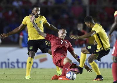 Panama's Blas Perez (centre) is marked by Jamaica's Jermain Taylor (left) and Lee Williamson during their FIFA World Cup 2018 qualifier in Panama City yesterday. (Photo: AFP)