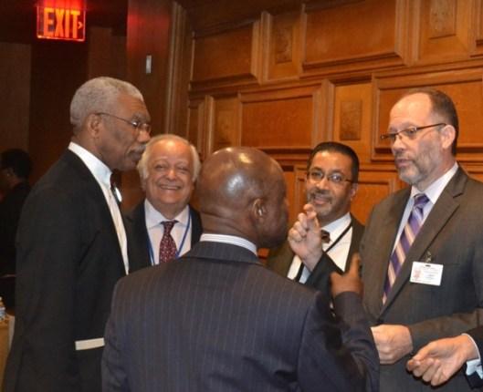 President David Granger, veteran Guyanese diplomat, Sir Shridath Ramphal, CARICOM Secretary-General, Mr. Irwin LaRoque, Minister of Foreign Affairs, Mr. Carl Greenidge (backing camera) and another official share a light exchange.