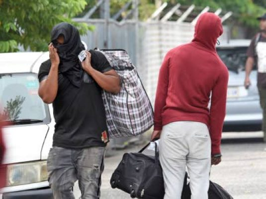 One of the 42 people who were deported from the United Kingdom on Wednesday covers his face to shield his identity as he leaves the police Mobile Reserve facility in the Vineyard Town area of Kingston. (Photo: Michael Gordon/ Jamaica Observer)