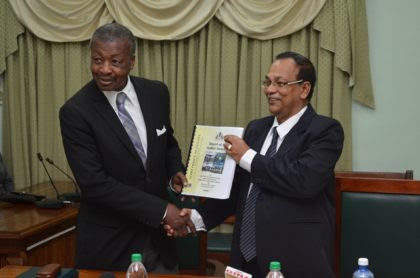 Dr. Barton Scotland, C.C.H, MP receiving the Auditor General Report from Deodat Sharma, Auditor General of Guyana.