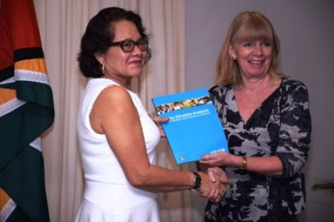 First Lady Sandra Granger receives a copy of the Situation Analysis of Children and Women from UNICEF Representative Marianne Flach.