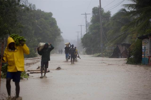 Residents walk in flooded streets as they return to their homes in Leogane, Haiti on Oct. 4. Matthew slammed into Haiti's southwestern tip with howling, 145 mph winds Tuesday, tearing off roofs in the poor and largely rural area, uprooting trees and leaving rivers bloated and choked with debris