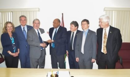 Natural Resources Minister  Raphael Trotman (centre) receives the letter of notification from Jeff Simons, Country Manager of ExxonMobil along with representatives from Nexen Energy and Hess Corporation at the Ministry of Natural Resources Boardroom, Brickdam