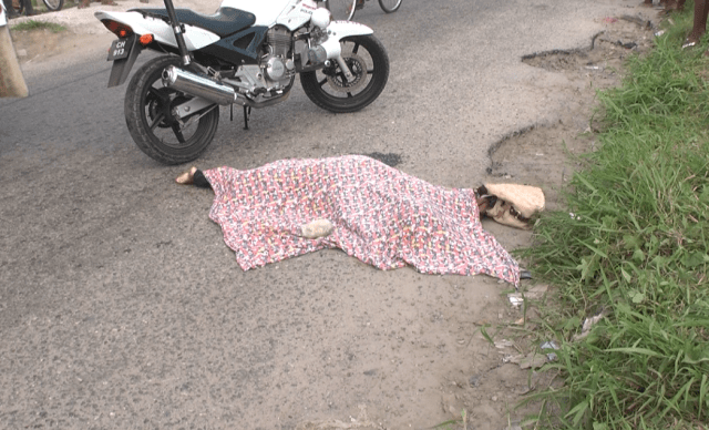 The body of the dead woman covered on the roadside