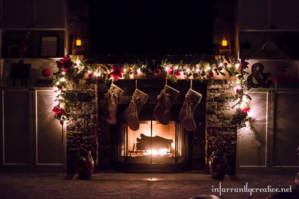 rustic fireplace decorated for CHristmas at night