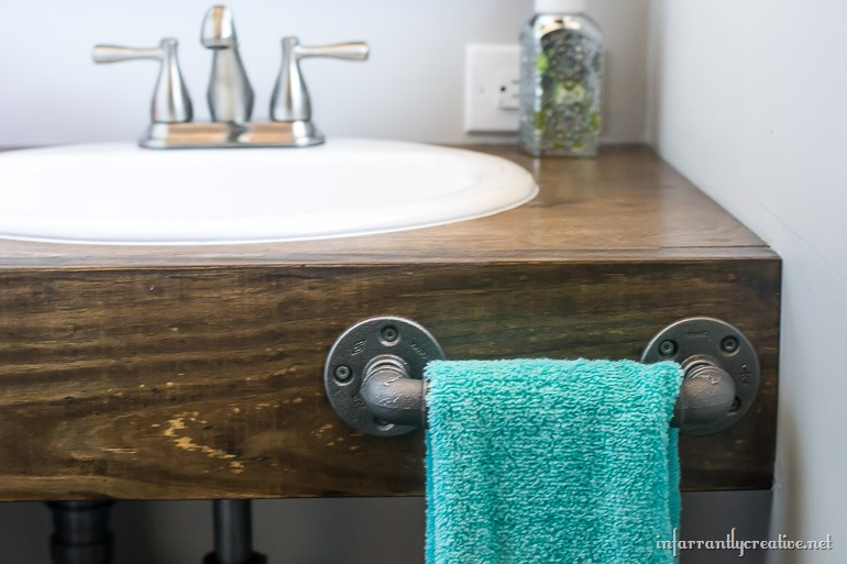 Fancy The vanity area is small but I think it is perfect for a guest bathroom And I absolutely love the dark wood vanity top paired with the gray tones in the
