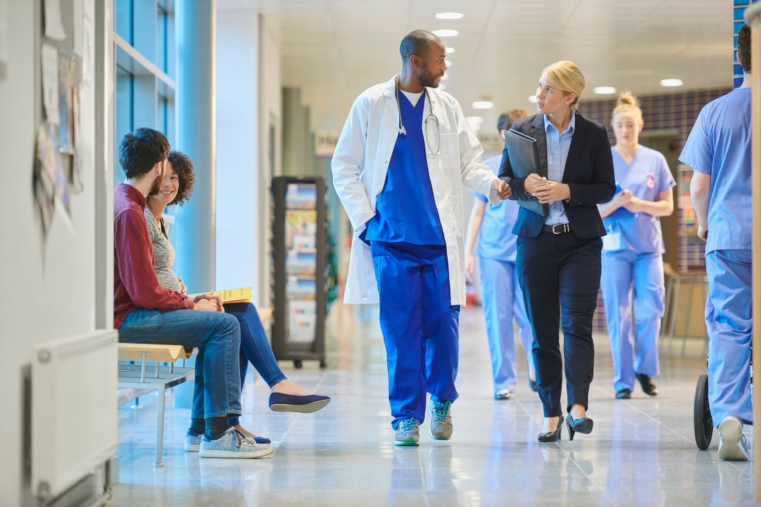 Physician and business woman walking in the hall of a hospital.