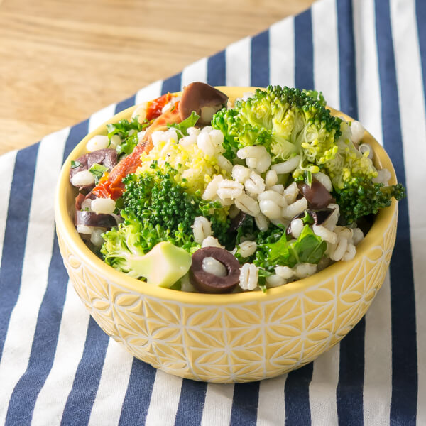 small yellow bowl on a blue striped napkin with broccoli, barley and olive salad