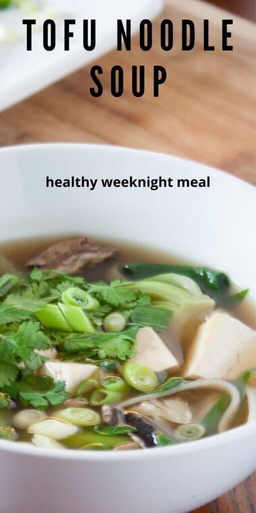 tofu noodle soup in a white bowl with greens