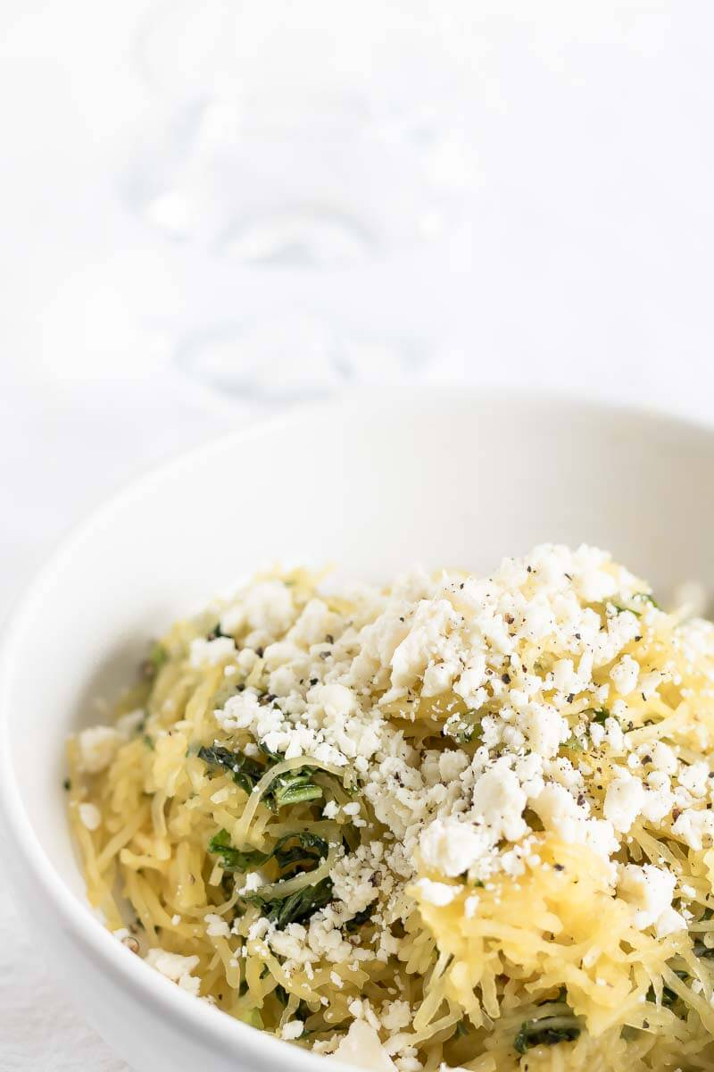 A bowl of cooked spaghetti squash with feta and kale.