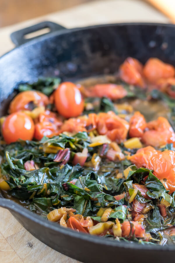 swiss chard and blacken cherry tomatoes in a cast iron skillet