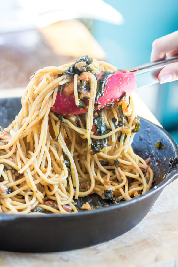 tossing pasta with swiss chard and blackedn tomatoe sauce in a skillet