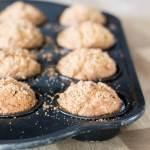 a muffin tin full of pumpkin butter muffins with cinnamon sugar