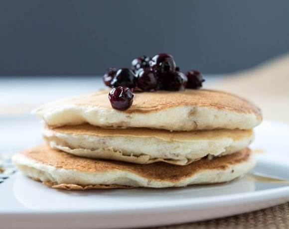 a stack of dairy-free pancakes with blueberries on top