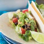 taco bake served in soft taco shells with lettuce and lime