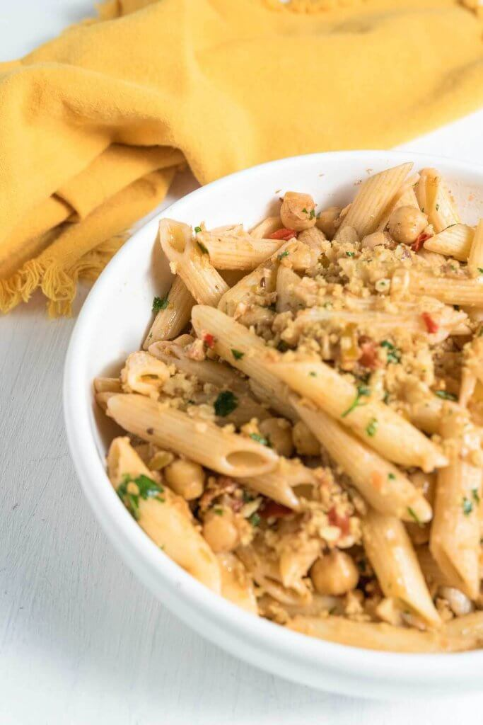 chickpea and olive pasta with toasted breadcrumbs and herbs, in white serving bowl