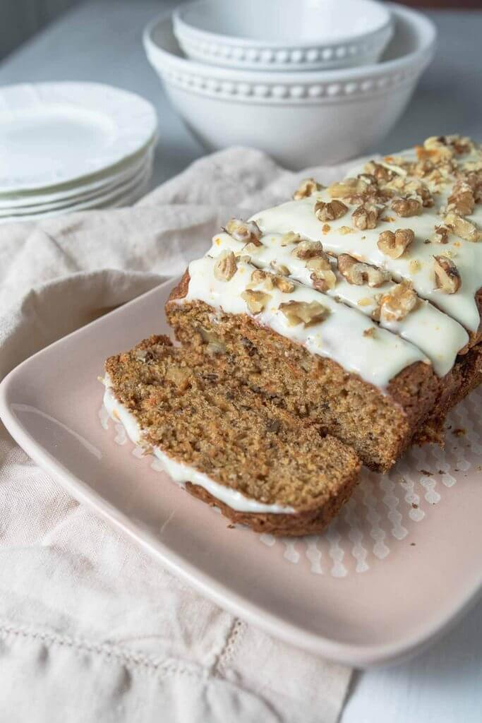carrot loaf with cream cheese frosting and walnuts on a plater