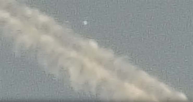 UFO leaving chemtrail - A man records a UFO coming out of a chemtrail